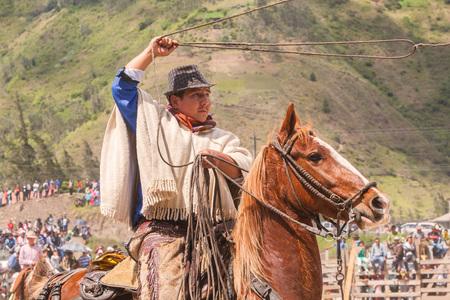 layman: Banos, Ecuador - 30 November 2014: Latin Indigenous Cowboy Riding A Horse And Throws A Lasso, South America In Banos On November 30, 2014 Editorial