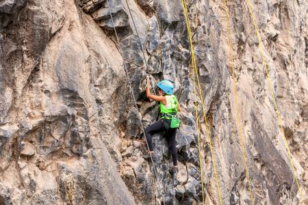 tenacious: Banos, Ecuador - 30 November 2014: Basalt Challenge Of Tungurahua, Tenacious Girl Climbing A Rock Wall In Banos On November 30, 2014