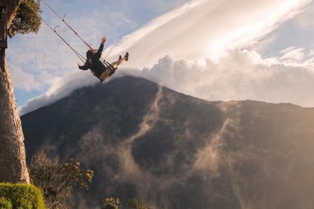 columpios: Silueta de una mujer joven feliz en un columpio, balanceo Sobre las montañas de los Andes, Tungurahua volcán en el fondo, de árbol, Ecuador