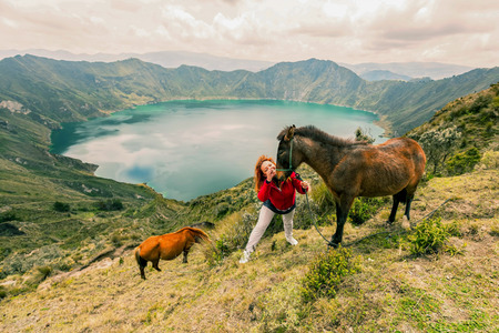 Blonde Woman Playing With Two Horses In The Lake Quilotoa