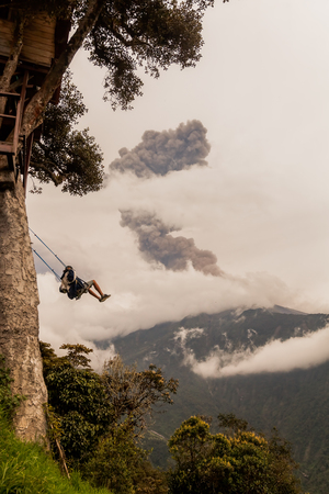 Unidentified Silhouette Of Young Teenager Man On A Swing, Casa Del Arbol, The Tree House, Tungurahua Volcano Explosion On March 2016 In The Background, Ecuador, South America Stock Photo