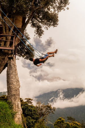 Unidentified Silhouette Of Relaxing Teenager Man On A Swing, Casa Del Arbol, The Tree House, Tungurahua Volcano Powerful Explosion On March 2016 In The Background, Ecuador, South America