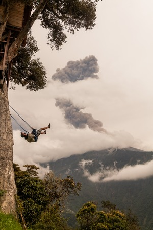 eruptive: Banos De Agua Santa, Ecuador  - 08 March 2016: Silhouette Of A Happy Young Teenager Boy Swinging On A Swing Above The Andes Mountains, Tungurahua Volcano Explosion March 2016 In The Background, South America In Banos De Agua Santa On March 08, 2016