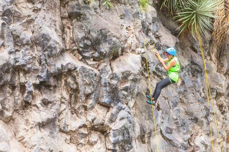 carabineer: Banos, Ecuador - 30 November 2014: Basalt Challenge Of Tungurahua, Teenager Latin Girl Climbing A Vertical Rock Wall, South America In Banos On November 30, 2014 Editorial