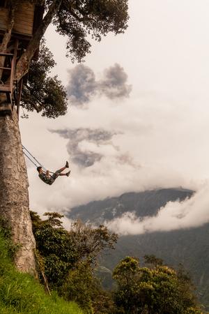 Banos De Agua Santa, Ecuador - 08 March 2016: Unidentified Man Swinging On A Swing In Banos De Agua Santa, Tungurahua Volcano Explosion On March 2016 In The Background, Ecuador, South America In Banos De Agua Santa On March 08, 2016