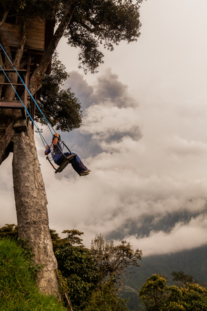 eruptive: Banos De Agua Santa, Ecuador - 08 March 2016: Happy Child Swinging On A Swing At Sunset, View from Casa Del Arbol,  The Tree House, Tungurahua Volcano Explosion On March 2016 In The Background, Ecuador In Banos De Agua Santa On March 08, 2016 Editorial