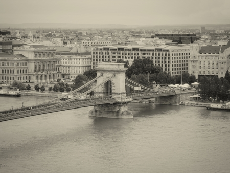 the chain bridge: Szechenyi Chain Bridge Is A Suspension Bridge That Spans The River Danube Between Buda And Pest, The Western And Eastern Sides Of Budapest, The Capital Of Hungary, Monochrome Shoot Stock Photo