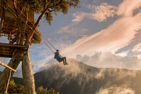 Banos De Agua Santa,  Ecuador - 25 November 2015: Teenager Boy Is Taking A Ride On The Wildest Swing In The World Made Of A Metal Beam Simply Attached To A Rope With No Safety Belts, South America