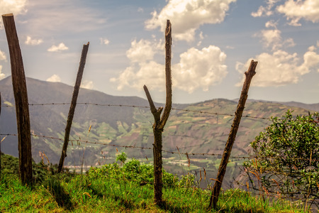 Old Wood Fence Posts With Barb Wire, Aerial View Of Andean Cordillera In The Background, Ecuador, South America