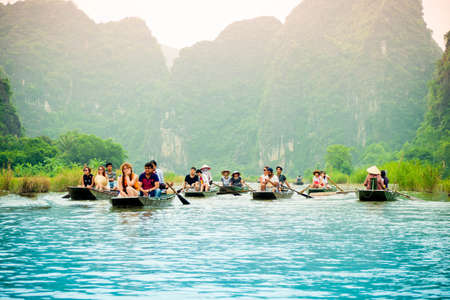cruising: lake landscape and cruising old wooden boat on the lake in summer at Vietnam. Editorial