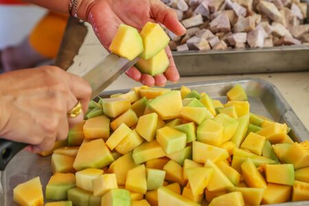 lady slices yellow color fruit in kitchen