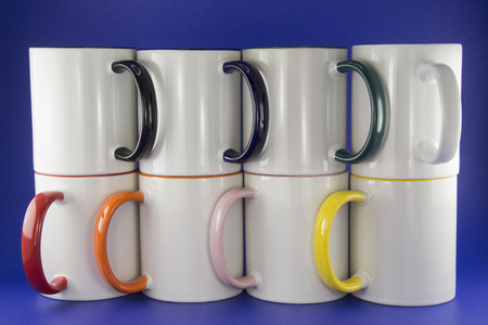 white cup with multi-colored handles on a blue background