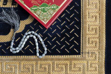 Muslim Holy Quran and rosary or tasbih with praying mat rug or sejadah Stock Photo
