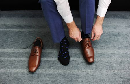 The business men is putting on her shoes