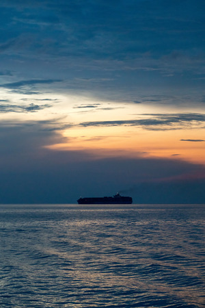 Container ship sail along the trade route in the evening before sunset