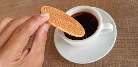 Dipping famous traditional Dutch waffle called Stroopwafel into black coffee