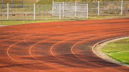 Old athletic racetrack and green grass field in the football stadium Standard-Bild - 97057152
