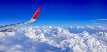Right wing of jet plane over cloudy sky Stock Photo
