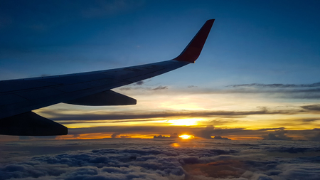 Silhouette of jet planes wing over the clouds at high altitude when sunset. Stock Photo