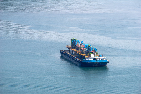 Flat top barge carries structures that seem to be an oil rig, oil platform or even the structures inside a ship. Imagens