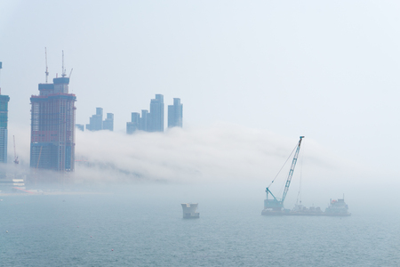 Thick large and heavy mist blow from the sea to the land and pass through shop near shore and skyscrapers inland and cover all other buildings in the area.