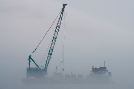 Crane barge in the middle of heavy mist blow from the sea. Banque d'images