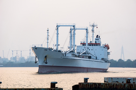 White reefer ship or refrigerated cargo ship sails in Chao Phraya river in the evening with power plants in the background.