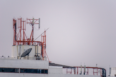Group of communication posts with so many frequency radio antennas and TV satellite dish on the roof top of the tall building.
