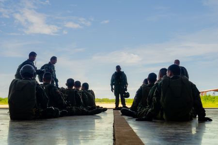 CHONBURI, THAILAND - JUNE 14, 2018 : Parachute team leader briefs his full gear equiped troops in the airplane hangar before doing a mission. Editorial