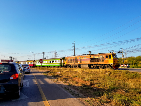 UDONTHANI, THAILAND - FEBRUARY 26, 2018 : Cars in both lanes stop at the intersection waiting for the train crossing the street on February 26, 2018 in Udonthani, Thailand.