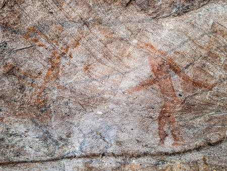 Prehistoric painting of men in actions on rock painted with red colour by human who live in the area over thousand year ago. These painting located in Phu Phra bat historic park, Udon Thani, Thailand.