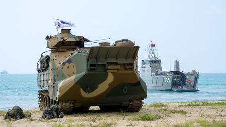 CHONBURI, THAILAND - FEBRUARY 17, 2018: Assault amphibious vehicle of South Korea and Royal Thai Navy amphibious ship land on sea shore during Cobra Gold 2018 Multinational Military Exercise. Sajtókép