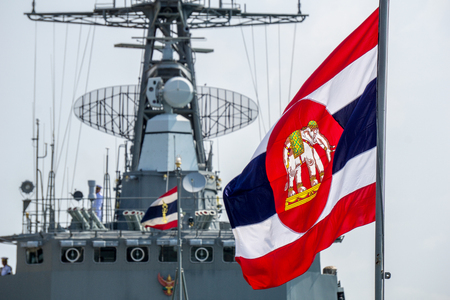 CHONBURI, THAILAND - MARCH 15, 2018 : Royal Thai Navy ensign blow on flag pole with Royal Thai Navy Frigate in the background on March 15, 2018 in Lamthien Naval Base, Chonburi, Thailand. Editorial