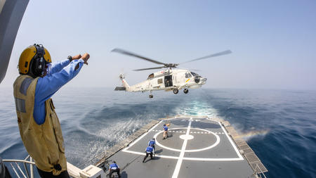 CHONBURI, THAILAND - JANUARY 29, 2014 : Helicopter deck officer give hand signal to Sikorsky S-70 Sea Hawk helicopter hovering above helicopter deck of Thai Navy ship to receive supplies.