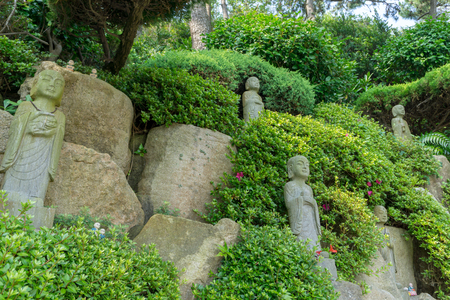 BUSAN, SOUTH KOREA - JULY 20, 2017 : Chinese priest stone sculptures in the garden of Haedong Yonggungsa Temple on July 20, 2017 in Busan, South Korea.
