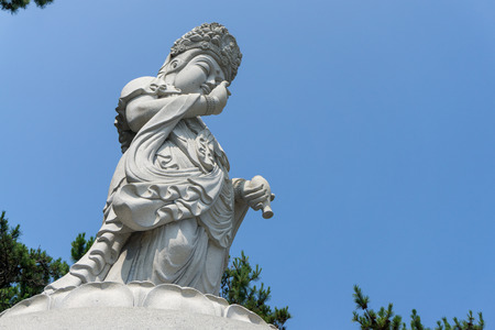 BUSAN, SOUTH KOREA - JULY 20, 2017 : Guanyin or Guan Yin Goddess of Mercy white stone statue on the top of the hill at Haedong Yonggungsa Temple on July 20, 2017 in Busan, South Korea. Editorial