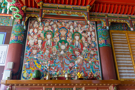 BUSAN, SOUTH KOREA - JULY 20, 2017 :  Colour painting of Buddha and buddhism gods images on the wall in Main hall of Haedong Yonggungsa Temple on July 20, 2017 in Busan, South Korea.