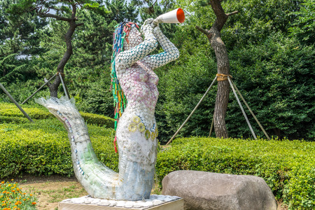 BUSAN, SOUTH KOREA - JULY 20, 2017 : Mermaid sculpture made from recycle waste display in the public park in Haeundae Dongbaekseom Island on July 20, 2017 in Busan, South Korea. Editorial