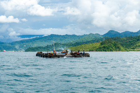 PADANG, INDONESIA - APRIL 11, 2016 : Small tugboat carries pontoon to ship that anchoring in Padang bay for harbor service on April 11, 2016 in Padang, Indonesia. Editorial