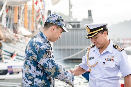 PADANG,INDONESIA - APRIL 13, 2016 :  Royal Thai navy officer in white uniform shakes hand with PLAN officer in blue digital camouflage pattern uniform during Multilateral Naval Exercise Komodo 2016.