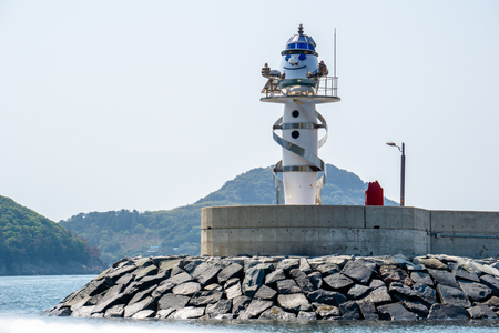 GEOJE,SOUTH KOREA - APRIL 28, 2018: Gujora Hang South Breakwater, a round white metal lighthouse decorated with amusingly metal bands spiralling around the tower and a Geoje mascot face at the top.