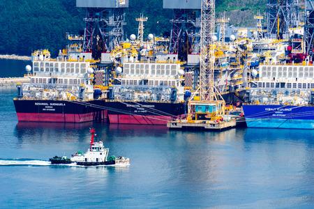 GEOJE ISLAND, SÜDKOREA - 20. MAI 2018: Tugboat segelt driil Schiffe in der Bucht von Daewoo Shipbuilding and Marine Engineering (DSME) in Okpo City, Südkorea.