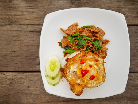 Hot and spicy fried fermented pork with , basils and green long beans served with white rice, crispy fried egg , sliced cucumber and red chillies on white dish over wooden table.