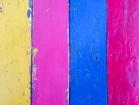 wooden plank painted with colorful yellow, pink,blue and red color in stripes pattern.