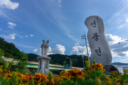 CHUNGCHEONGBUK, SOUTH KOREA - SEPTEMBER 25, 2018: Soldiers rock statue and Korean language craving monolith at the roundabout near Haengchon crossroads bicycle certification center in Yeonpung-myeon. Standard-Bild - 110498681