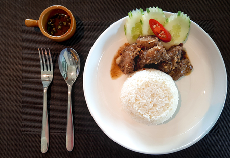 Chopped pork ribs fried with garlic eat with white rice garnished with sliced cucumber and red chilli served with fish sauce and fresh chillis with spoon and fork.