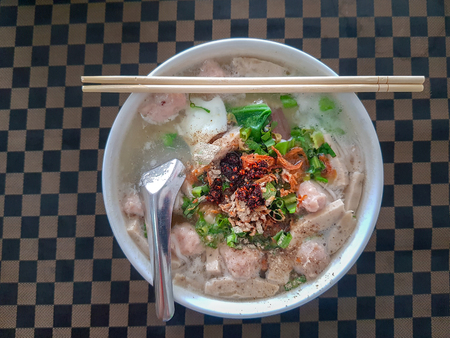 Vietnamese Rice Noodle Soup with pork chopped and sausage served in the white bowl on checker pattern dinner table with chopsticks and short spoon