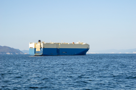 Large White and blue Roll-on/roll-off (RORO or ro-ro) ships or oceangoing vehicle carrier ship anchor in the open sea. Roro ship designed to carry wheeled cargo such as cars, trucks, trailers, etc. Foto de archivo