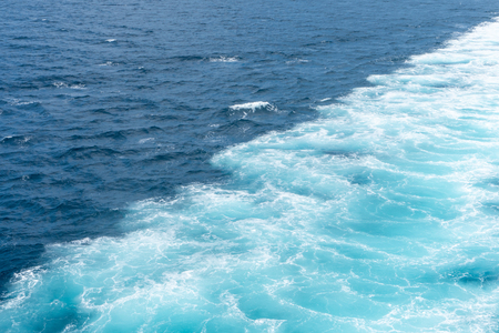 Wake of water created by ship that sailing through the calm sea water Stock Photo