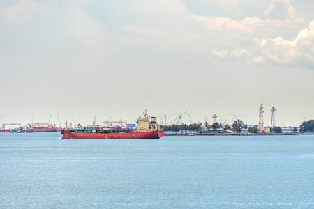 Red tanker sail pass industry and commercial port near Malacca strait in Indonesia territory